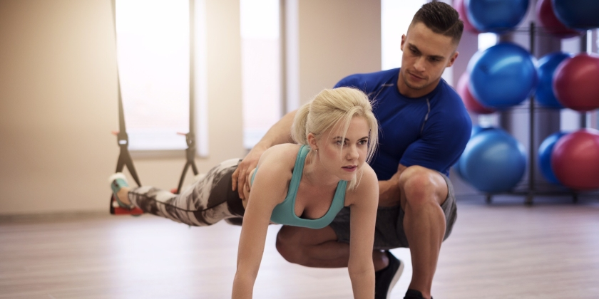 Frau macht mit Hilfe eines Personal Trainers Krafttraining