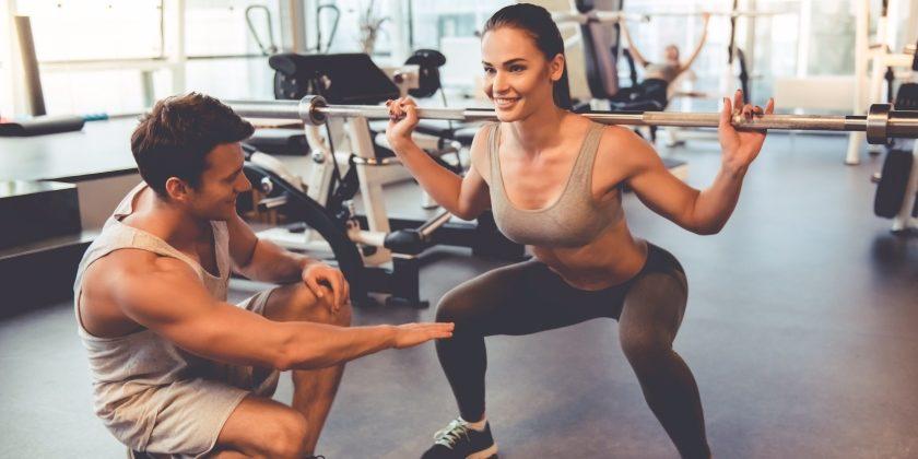 Frau macht unter Anleitung eines Personal Trainers Muskeltraining